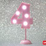 Número 4 gigante color rosa con luces