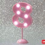 Número 8 gigante color rosa con luces